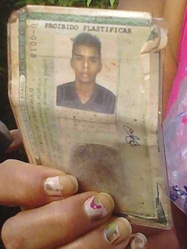 10 de março -Mãe mostra carteira de identidade de David Santos Souza, limpador de vidros de 21 anos que perdeu o braço no acidente