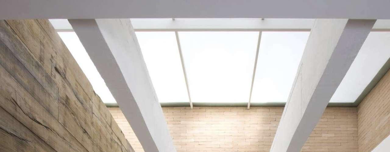 O grande painel de madeira recobre toda a parede do espaço com pé-direito duplo, preenchendo o ambiente