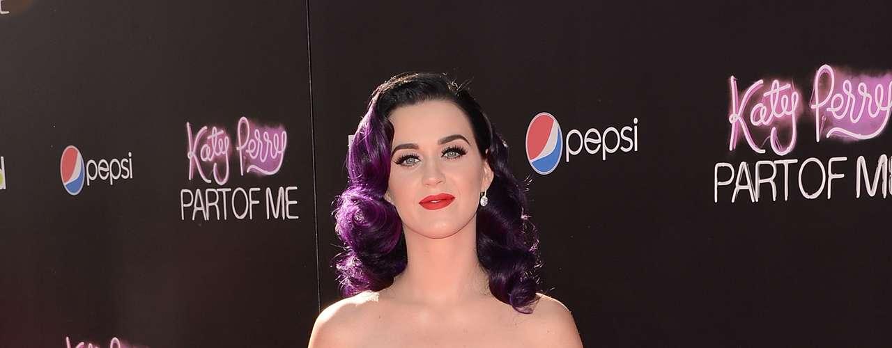 Katy Perry optou por um vestido tomara que caia com a saia bem godê de veludo vermelho, mesmo tom dos sapatos. Tudo da grife Dolce & Gabbana. Uma opção bem chique, mas que pode ser perigosa se a pessoa tiver uns quilinhos extras, pois pode parecer uma poltrona