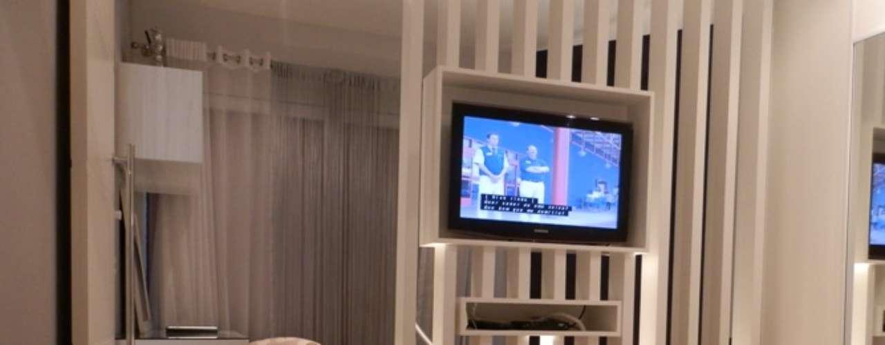 A arquiteta criou um painel que serve como divisória e nicho para TV.