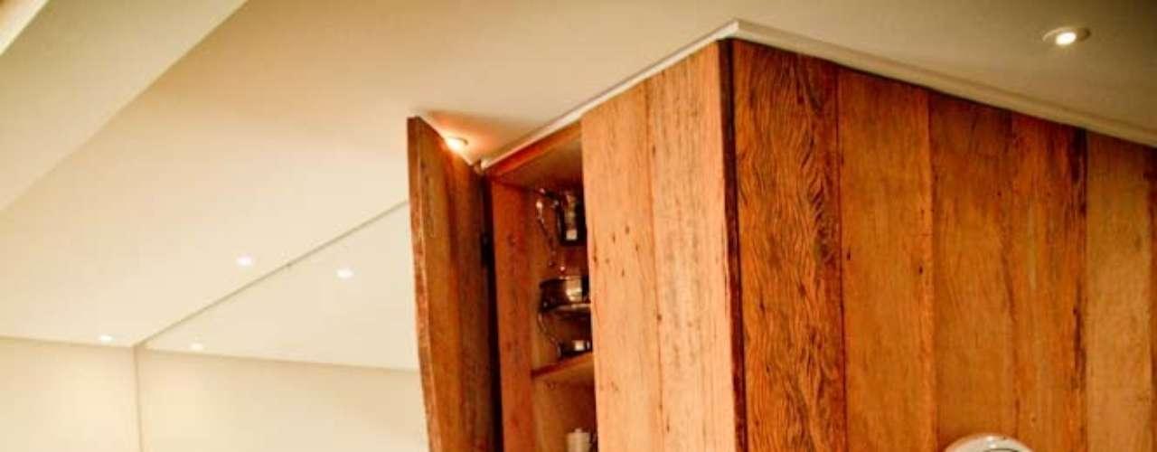 ...mas também esconde um armário e dá um toque de conforto ao ambiente, integrando a cozinha ao resto do ambiente. Neste apartamento, a madeira está em vários outros lugares...