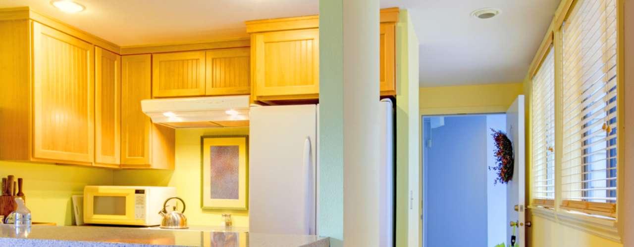 Por integrar ambiente, a cozinha americana permite que a decoração use elementos diferentes, como a madeira e o mármore, usado neste projeto para fazer o balcão