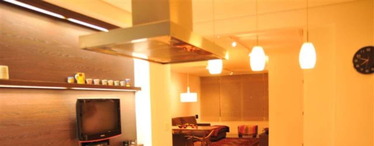 Na mesma cozinha, a arquiteta separou a bancada para refeições do tablado onde fica o fogão. Na parede, ainda sobrou espaço para uma televisão