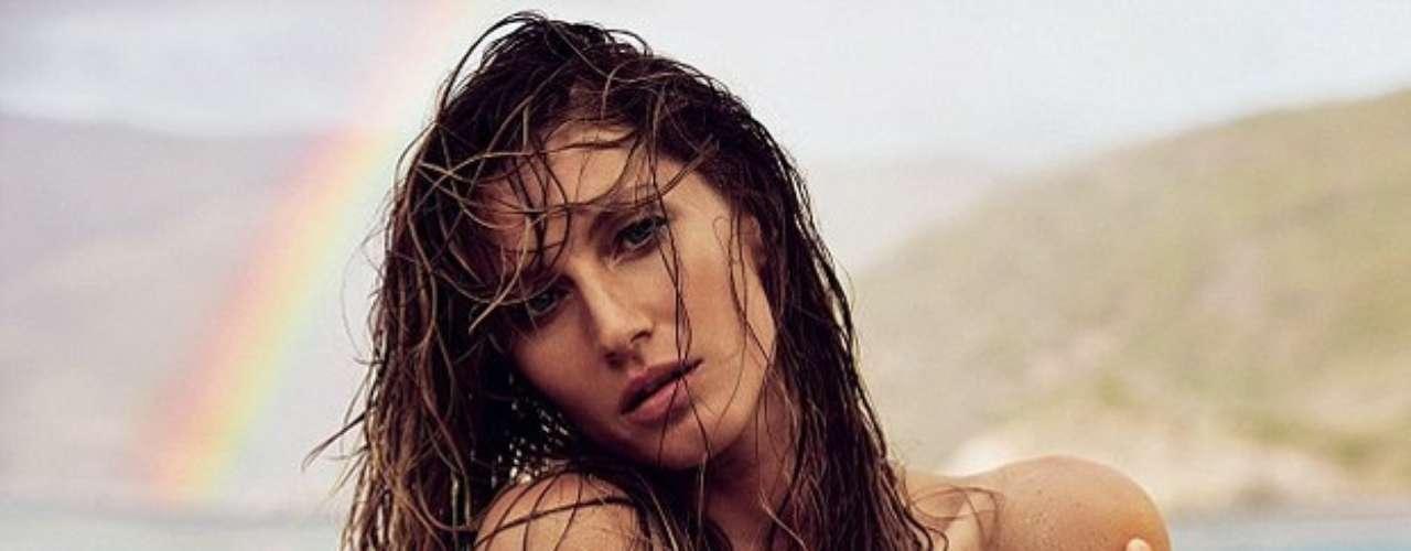 Gisele, que está prestes a completar 32 anos, aparece deitada em uma praia paradisíaca. Coberta por areia, a modelo também posou de topless, cobrindo os seios apenas com os braços