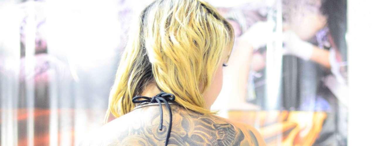 Esta tatuadora tem um desenho grande que vai do pescoço até a perna
