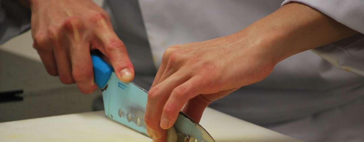 O preparo começa com o corte central da peça de vieira