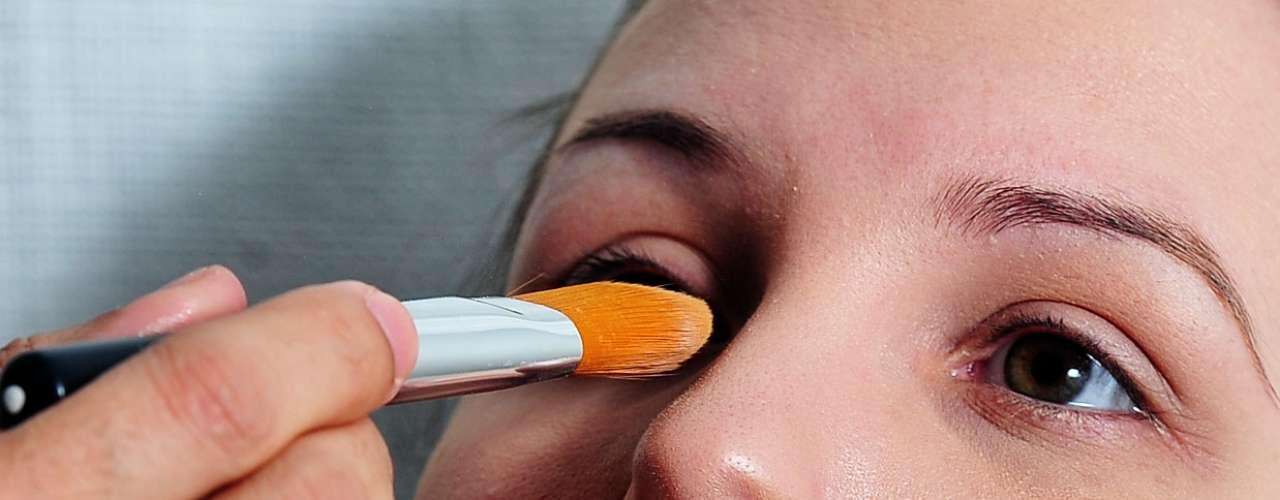 Com um pincel menor, ele faz a correção das imperfeições da pele, usando a própria base