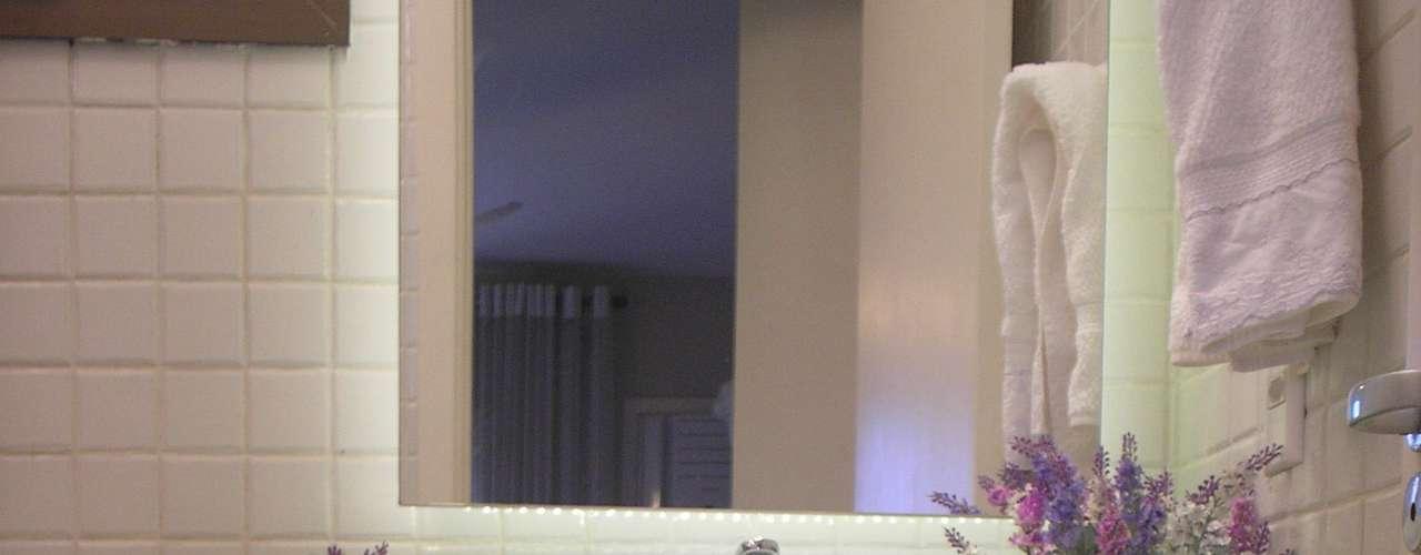 O vaso de lavandas e os puxadores em lilás e verde complementam a decoração do banheiro