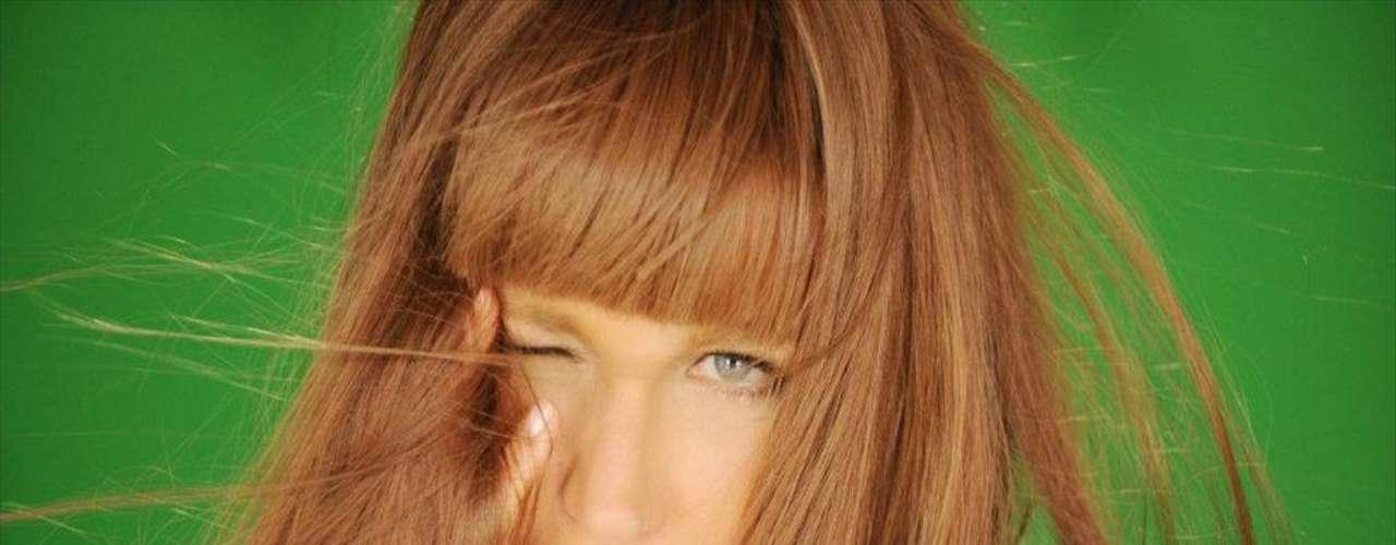 Em outra imagem, xuxa aparece com uma peruca longa, com franja e fios castanhos