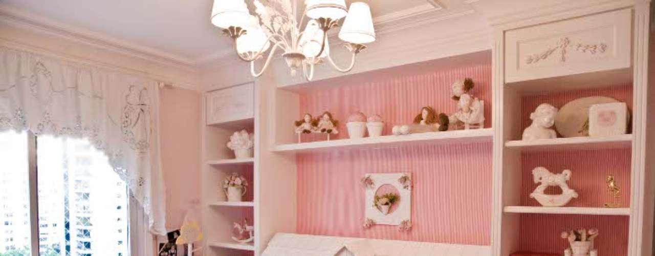 A parede forrada de tecido (uma tendência) combina com o revestimento do sofá. A casinha de bonecas virou estante