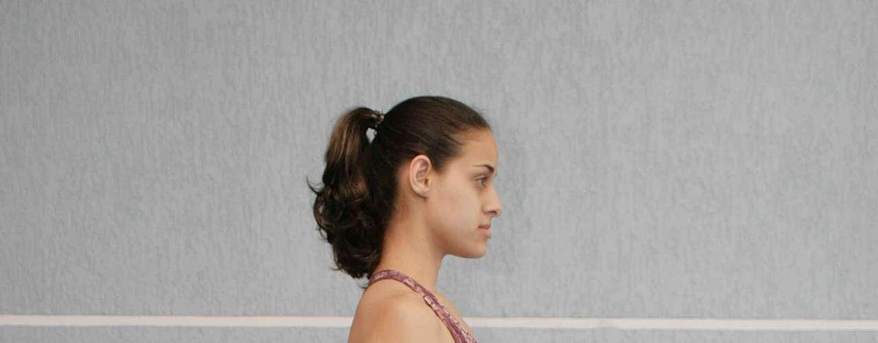 Certo: no primeiro exercício, coloque a parte elástica do rubber embaixo do pé direito ou esquerdo, fique com a coluna ereta e mantenha os braços ao lado do corpo