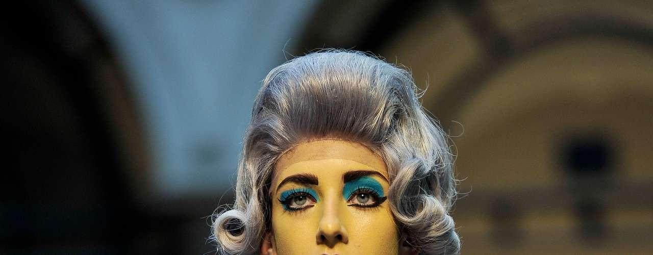 Nem a maquiagem marcante e a peruca desviaram totalmente a atenção do broche de pênis usado pela modelo no desfile de Vivienne Westwood Red Label