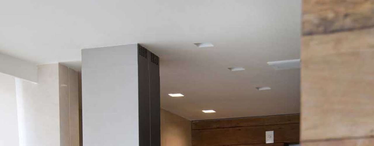 O mármore espanhol Crema Marfil usado no piso foi também empregado na parede da pia, contrapondo-se à parede oposta, revestida com madeira de demolição