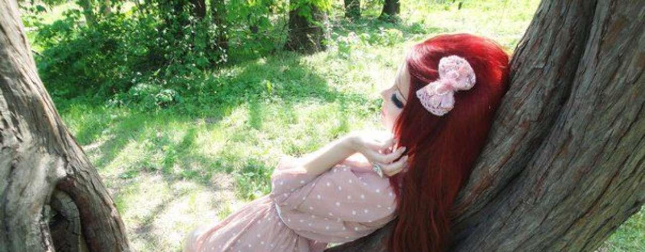 Anastasiya posa para fotos em cenários bucólicos, como jardins com borboletas