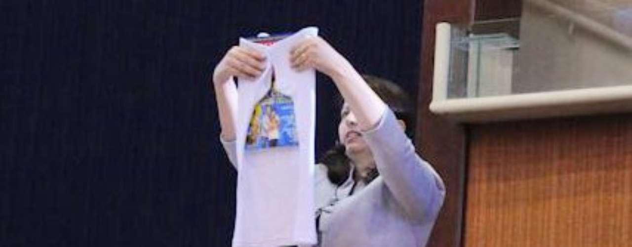 A parte da frente da camiseta fica para baixo e a revista deitada é colocada logo baixo da gola, na parte de trás