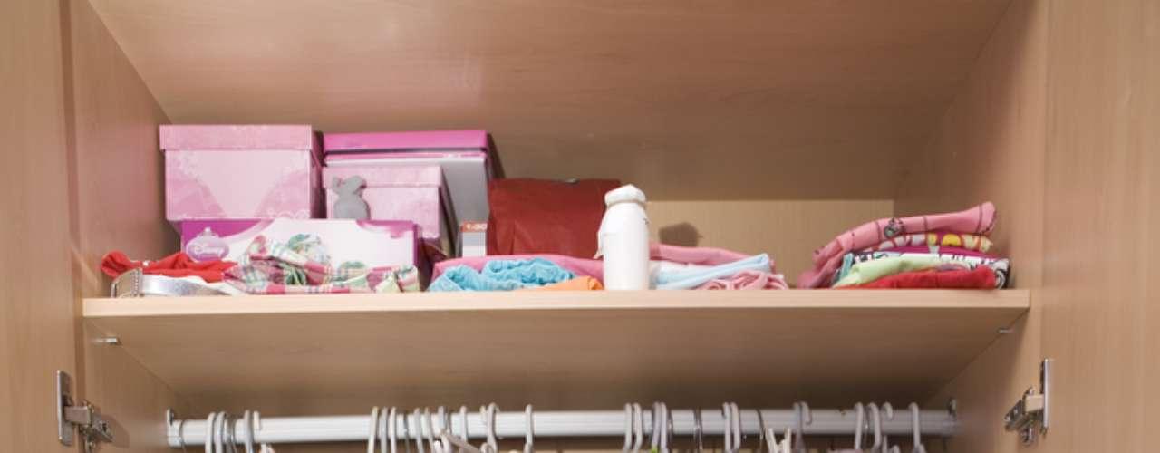 Este armário de criança está organizado de acordo com o que é mais usado. Vestidos e casacos estão pendurados. As camisetas estão dobradas na prateleira superior e dividem o espaço com os sapatos, que permanecem nas embalagens originais. Os itens mais delicados ficam na caixa organizadora de plástico, ao lado das bolsas para guardar fraldas e brinquedos