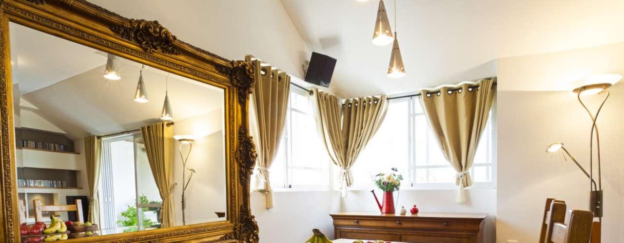 Junto à mesa de jantar, o espelho substitui um quadro e ajuda a refletir parte da luz que entra pela janela
