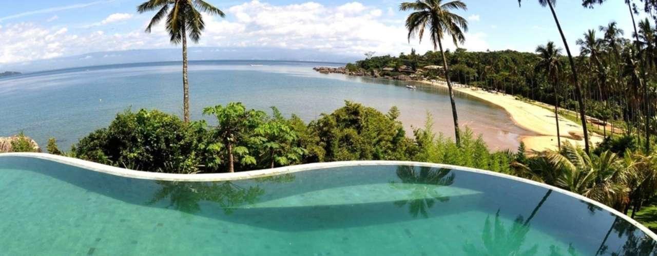 Como a casa ficava em um ponto mais alto que os arredores, o arquiteto João Marques instalou a piscina na beirada do terreno e usou borda infinita para valorizar a paisagem