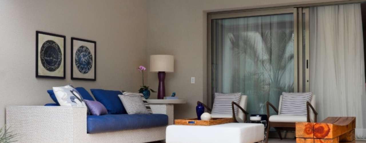 Os móveis da varanda, de madeira e fibra sintética, tem estofamento revestido com tecidos em azul e branco, repetindo os tons das pastilhas no fundo da piscina