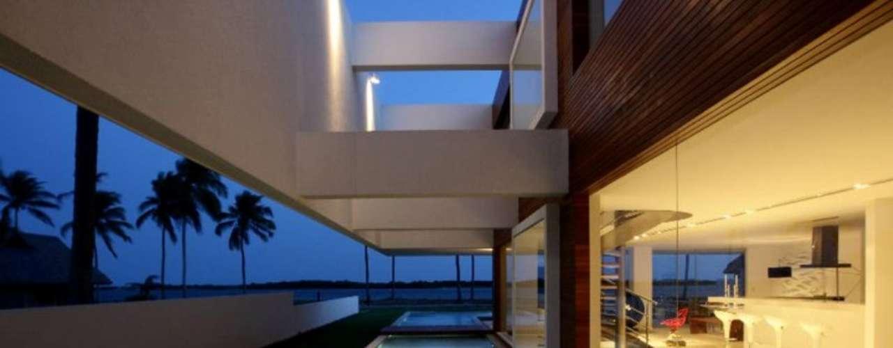 A piscina também desempenha um papel decorativo importante. Aqui, ela serve de cenário para quem circula pela sala e pela área gourmet, ambas com paredes de vidro
