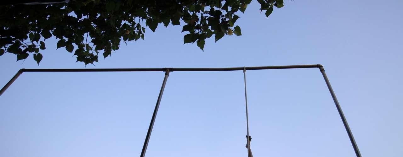 Com apenas um pé pendurado em uma corda, menina participa de aula de mallakhamb em Mumbai