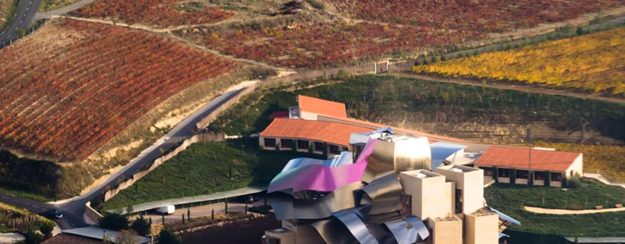 Hotel Marques de Riscal (Espanha): o telhado surpreendente é feito em aço prateado e dourado e titânio lilás, cores inspiradas nas tampas de prata, malha de fio de ouro e conteúdos roxos de uma garrafa de Marqués de Riscal. Mas as formas liquescente do telhado também evocam os prazeres do vinho em geral. O edifício é, em outras palavras, um instantâneo semi-abstrato de alguns vinhos da Gran Reserva girando em torno da bacia ampla de um recipiente grande