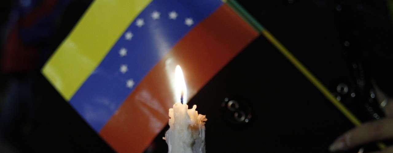 10 de dezembro -Boliviano segura vela e bandeira da Venezuela durante vigília pela saúde de Chávez em La Paz, na Bolívia