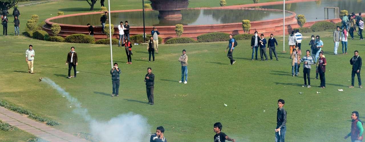 Jovem lança de volta uma bomba de gás lacrimogêneo jogava pela polícia