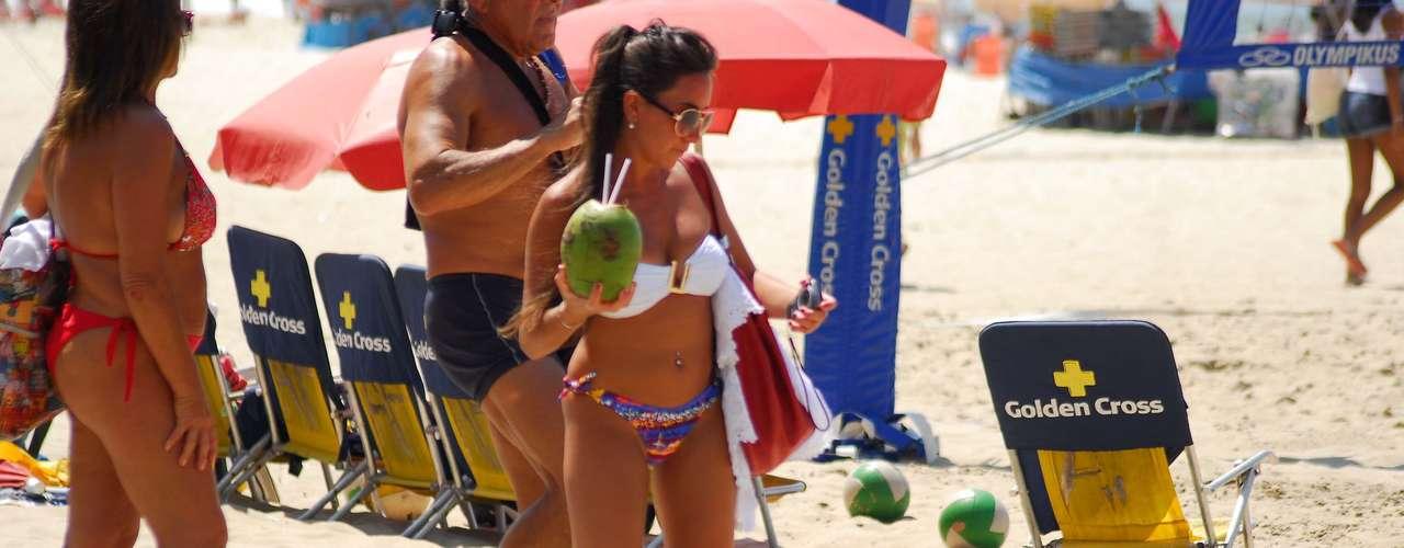 27 de dezembro - Jovem se refresca com água de coco na beira da praia