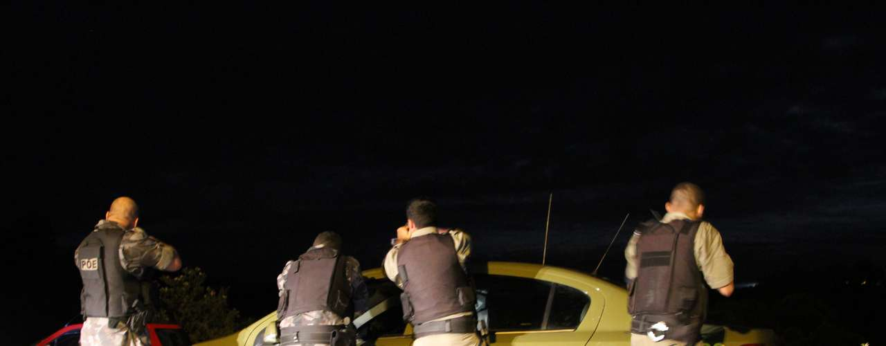 Policiais se protegem atrás de uma viatura durante as buscas aos assaltantes