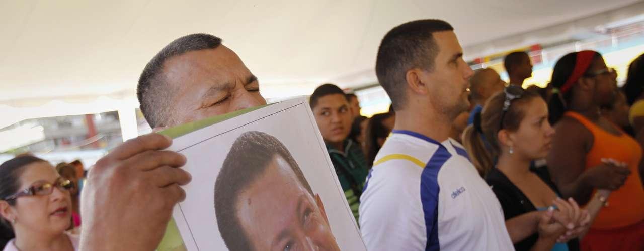 19 de dezembro - Simpatizante segura imagem de Chávez durante missa para rezar pela saúde do presidente, em Caracas. O chefe da Assembleia da Venezuela, Diosdado Cabello, disse nesta quarta-feira que, em sua opinião, poderia ser adiada a posse do presidente Hugo Chávez, marcada para o dia 10. Se Chávez não assumir, uma nova eleição pode ser convocada