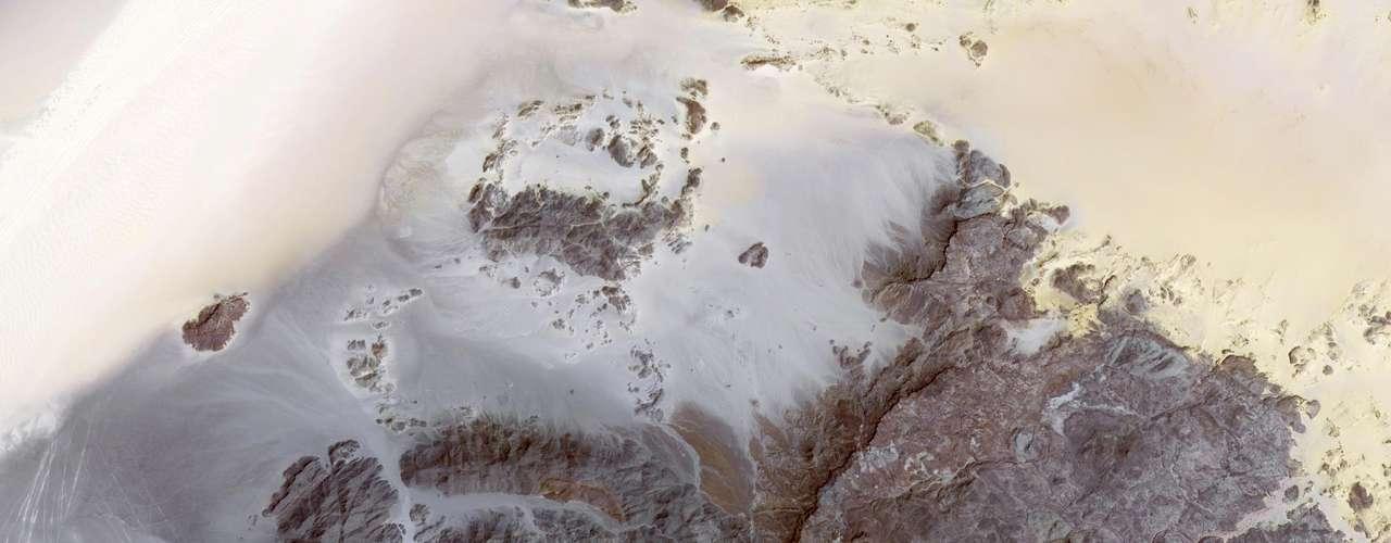 A cadeia de montanhas de Jebel Uweinat, na tripla fronteira entre Egito, Líbia e Sudão, é vista em imagem divulgada em 12 de janeiro pela Nasa. A área é notável pelos petróglifos (inscrições em rochas), que representam girafas, leões, avestruzes, gazelas e humanos em arte rupestre. Esse é um dos locais mais secos do mundo: registros indicam que lá não chove desde 1998