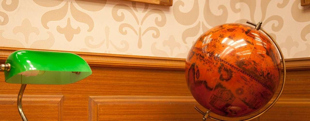 Entre os objetos decorativos do quarto se destacam os livros e mapas