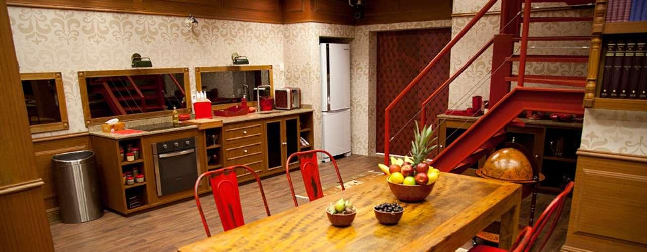 O espaço da biblioteca contém também uma segunda cozinha. Nela aparece uma mesa de jantar de madeira de demolição, combinada a cadeiras de ferro e sobre um tapete. \