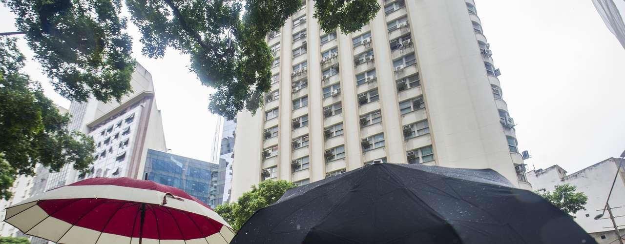 21 de janeiro Pedestres se protegem da chuva no centro do Rio de Janeiro
