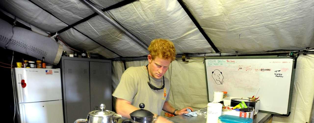 Sem regalias, o príncipe aparece nesta outra imagem limpando a cozinha do acampamento