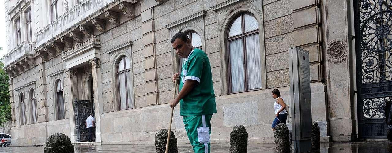 Funcionário limpa a calçada do Palácio do Catete após a chuva