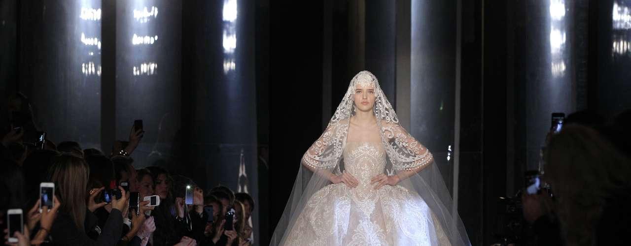Nesta quarta-feira (23), terceiro dia da semana de alta-costura de Paris, o desfile do estilista libanês Elie Saab chamou atenção ao mostrar um vestido de noiva rendado, com cintura marcada e saia com volume. Em peça única, o véu e a grinalda completaram o look