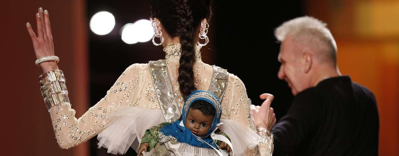 E quando a modelo virou de costas, detalhe para a boneca que carregava com trajes indianos