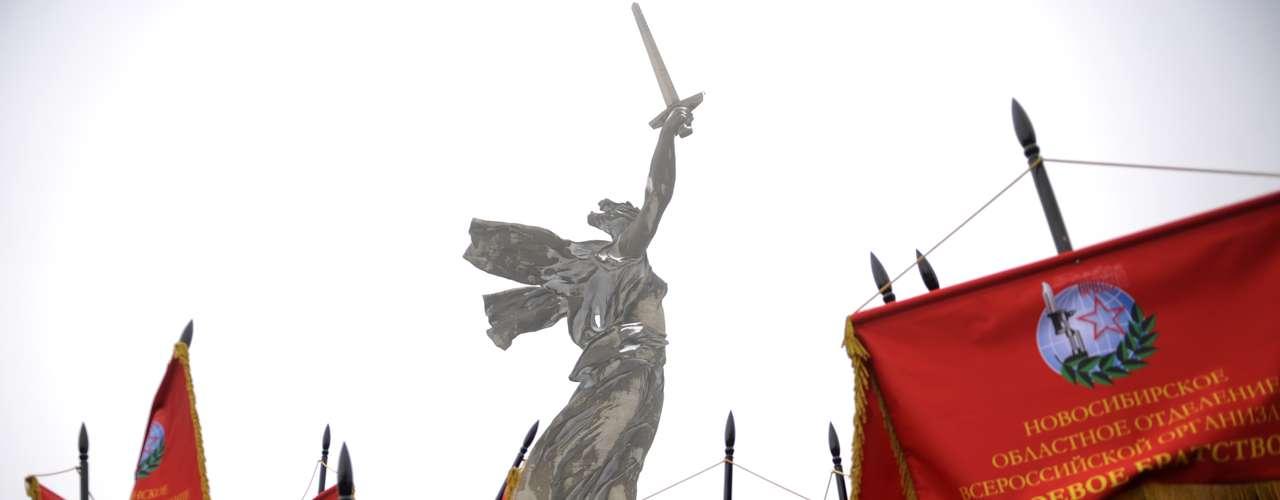Estudantes tremulam flâmulas vermelhas na base do monumento épico da Mãe-Pátria erigido em nome da força da Rússia e dos soviéticos