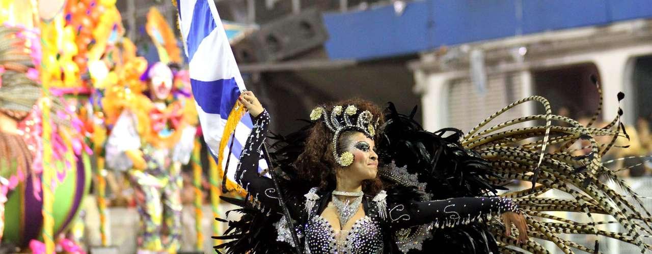 Vestidos com fantasias com plumas em marrom, preto e detalhes brancos, o primeiro casal de mestre-sala e porta-bandeira veio logo a frente do carro abre-alas