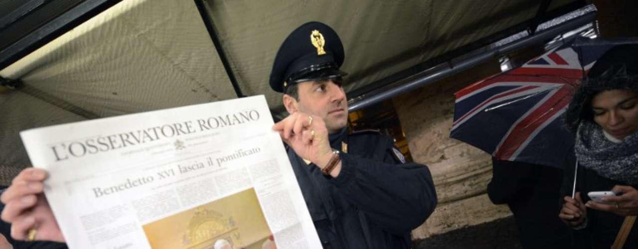 Um policial segura uma cópia do jornal do Vaticano, o L'Osservatore Romano, com a capa dedicada à renúncia do Papa Benedito XVI