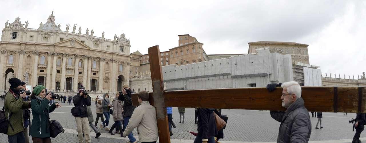 Fiéis carregam cruz na Praça São Pedro após o anúncio da renúncia do Papa