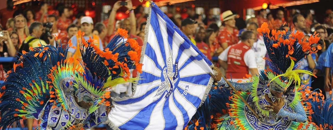Porta-bandeira e mestre-sala desfilam com o tradicional estandarte azul e branco da Portela