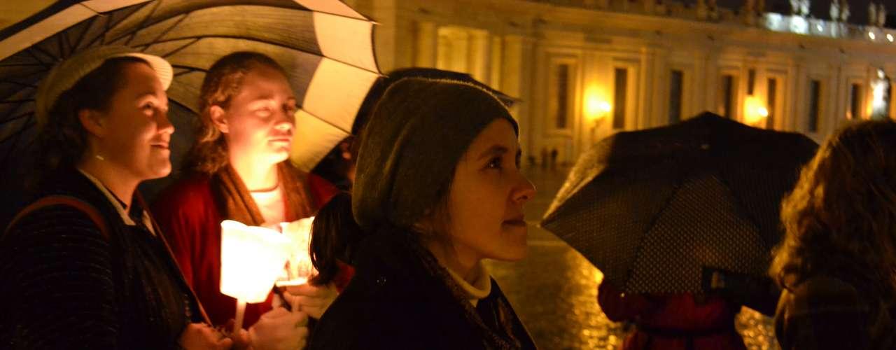 Corin Walters, dos Estados Unidos, protegia a chama da vela contra a chuva enquanto acompanhava um grupo de jovens de Roma que entoam músicas em homenagem a Joseph Ratzinger: vivo aqui em Roma e vim prestar meu apoio a decisão do Papa