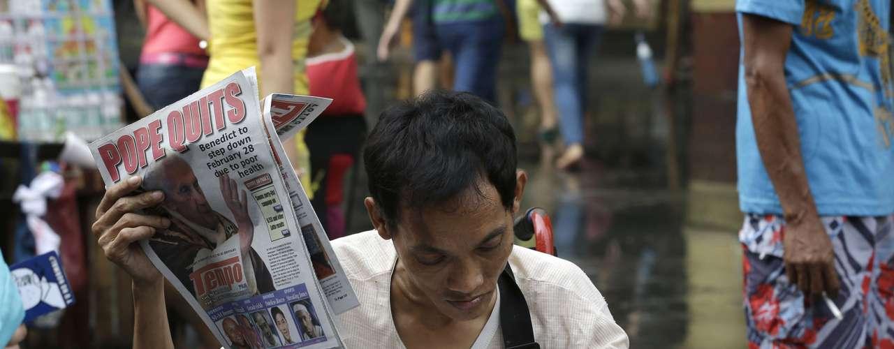 Em Manila, Filipino lê jornal com a notícia da renúncia do Papa