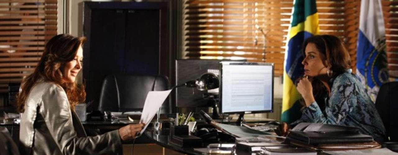 Lívia (Claudia Raia) se assusta quando percebe que Helô (Giovanna Antonelli) tem uma foto que comprova que ela esteve no banheiro onde Jéssica (Carolina Dieckmann) morreu