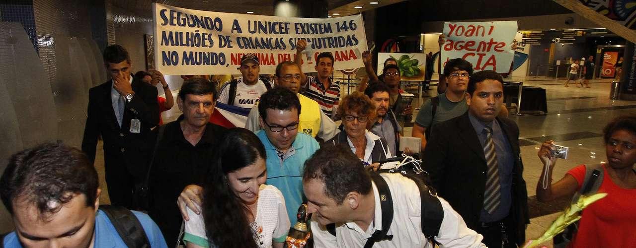 Yoani recebe um presente de seu amigo Dado Galvão (centro) após desembarcar no Brasil