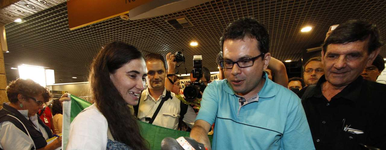 Com manifestantes contrários à sua visita ao Brasil ao fundo, Yoani é cumprimentada durante desembarque no aeroporto de Guararapes