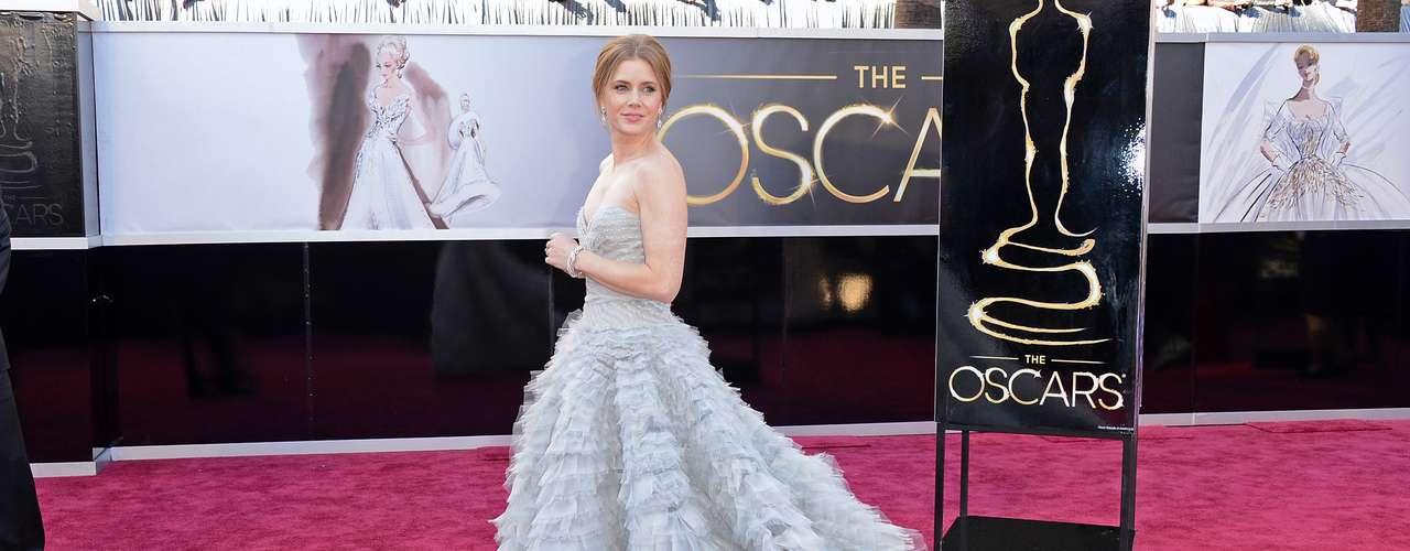 Amy Adams - O vestido tomara que caia meio cinza ou azul-claro Oscar de la Renta usado por Amy Adams traz babado na saia até a cauda e nervuras no dorso. Brincos pequenos e apenas um bracelete como acessórios. Ótima opção para um tapete vermelho que se preze, como o do Oscar.
